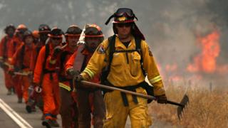 A Cal Fire firefighter leads a group of inmate firefighters in August