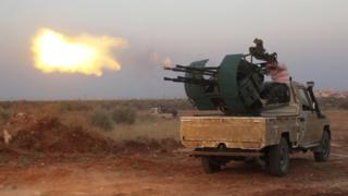 Rebel fighters fire a heavy machine gun during clashes with Syrian pro-government forces