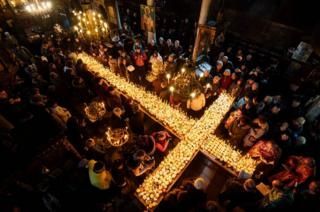 People pray around a cross-shaped platform covered with candles placed in jars of honey during a ceremony marking the day of Saint Haralampi, protector of beekeepers, at the Church of the Blessed Virgin in Blagoevgrad, on 10 February 2019.
