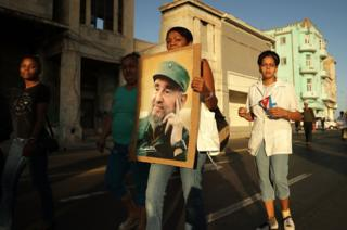 A woman carries a poster with the image of former Cuban President Fidel Castro
