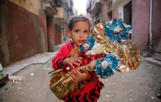 "Habiba, 6, hugs Aroset El Moulid or (Bride of Moulid) traditional sugar candy in the shape of dolls, in preparation for the celebration Prophet Muhammad""s birthday, in Tanta, north of Cairo, Egypt November 24, 2017. Picture taken November 24, 2017."