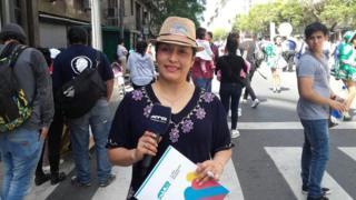 Jeannette sorri enquanto segura um microfone no meio de uma rua repleta de pessoas