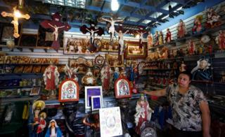 A woman stands inside a Christian souvenir shop