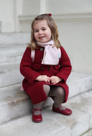 Princess Charlotte sits on the steps of Kensington Palace.