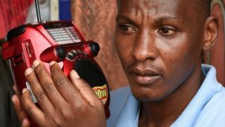 Mwanaume akisiliza redio kwa makini Uganda