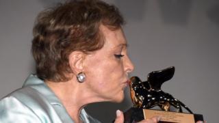 وسط تصفيق الجمهور المحتشد لحظة تكريمها، رفعت أندروز جائزة الأسد الذهبي وقبلتها