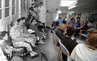 A composite image shows an NHS waiting room at the Montague Hospital, South Yorkshire, in 1959 and a waiting room at Milton Keynes University Hospital in 2018.