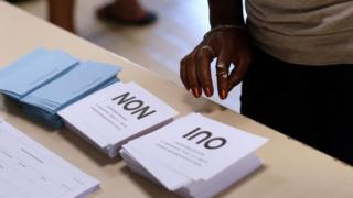 A voter looks at ballot papers in New Caledonia