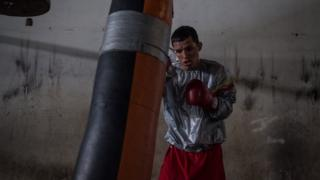 Boxer Robin Zamora trains with a punch bag