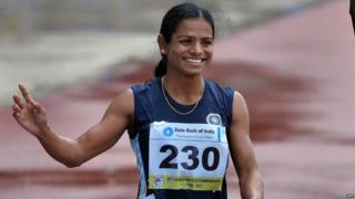 """In this photograph taken on July 7, 2013, women""""s 200 meters bronze medal winners from India, Dutee Chand waves to the crowd after the race on the fifth and the final day of the Asian Athletics Championship 2013 at the Chatrapati Shivaji Stadium in Pune."""