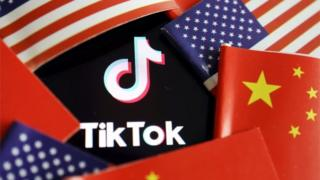 india The TikTok logo is seen here partly covered by a ring of alternating US and Chinese flags