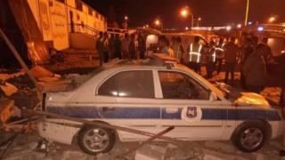 Escombros y un auto de la policía con daños tras el ataque aéreo en el este de Trípoli.
