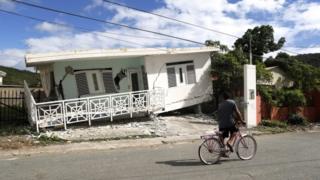 Una persona en bicicleta pasando frente a una casa dañada por el terremoto.