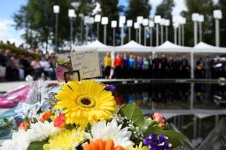 Flowers are left at the memorial as friends, relatives and victims commemorate the 20th anniversary of the IRA Omagh bombing at a ceremony in the Memorial Garden in Omagh
