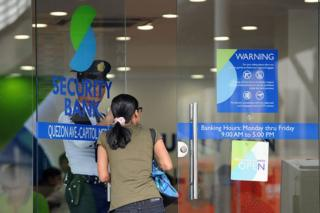 A customer enters a branch of the Security Bank in Manila on January 14, 2016