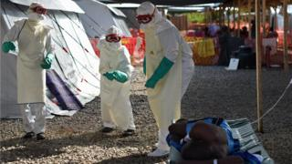 Health workers wearing a protective suit treats Ebola patients in West Africa