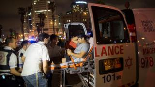 A wounded man is moved onto an ambulance after a stabbing attack in Jaffa, Israel (8 March 2016)