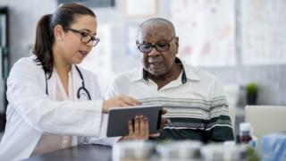 Profissional de saúde mostra algo para um idoso em uma tela
