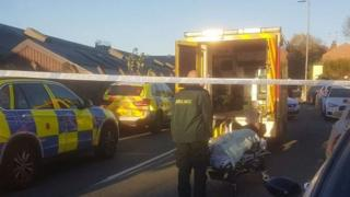 The injured policeman lies on a stretcher next to an open ambulance