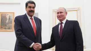 Russian President Vladimir Putin (R) and Venezuelan President Nicolas Maduro (L) shake hands during their meeting in the Kremlin