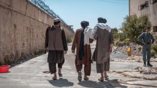 Prisioneros talibanes de espalda en el exterior.