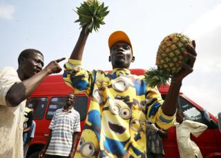 in_pictures A fruit seller in a Minions shirt holds up pineapples in Abuja, Nigeria - Thursday 9 April 2020