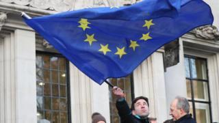 Человек с флагом ЕС перед зданием Высокого суда в Лондоне