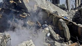 جندي سوري يرش الماء على موقع مركز سوري للابحاث تعرض إلى القصف