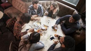 People sit at a pub table with crisps, drinks and phones