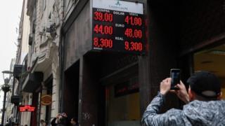 Hombre toma foto a casa de cambio en Argentina.