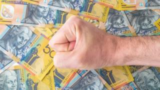 Punho sobre notas de dólares australianos