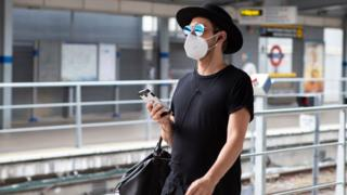 Man in a mask, sunglasses and a hat walks along a platform at a London Underground station with a phone in his hand