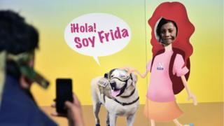 A girl poses for a picture through a banner depicting Mexican rescue dog 'Frida'