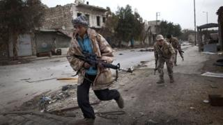 Syrian Turkmen rebels run across a street controlled by regime forces to dodge sniper fire in the Hanano district of the northern city of Aleppo in 2013