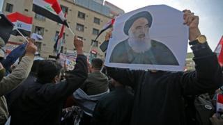 Sistani posteri taşıyan göstericiler
