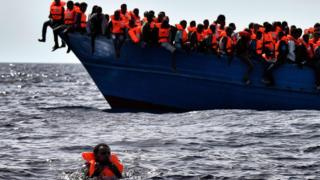 Migrants wait to be rescued as they drift in the Mediterranean Sea off the coast of Libya on 3 October