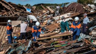 Search and rescue crews salvage belongings from the debris of buildings destroyed