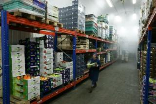 Workers prepare boxes of fresh fruit and vegetables ahead of distribution from a London warehouse
