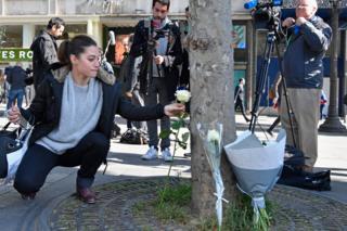 หญิงสาวคนหนึ่งวางดอกไม้ในที่เกิดเหตุโจมตีกลางกรุงปารีส