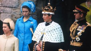 Prince Charles, wearing the crown after being invested with the title Prince of Wales, on a balcony with The Queen and Prince Philip
