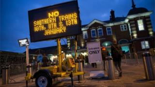 An information board advises passengers about strike action by Southern Rail outside Clapham Junction station