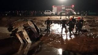 Jordanian civil protection services work on a road that was damaged by flash floods near Madaba, south of Amman, 9 November 2018
