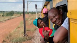 President Cyril Ramaphosa is seen smiling, gesturing and sticking his head out of a train window