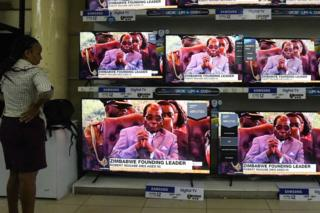A Kenyan woman watches news with the headline on the death of former Zimbabwean president Robert Mugabe, at an electronics shop in Nairobi on September 6, 2019