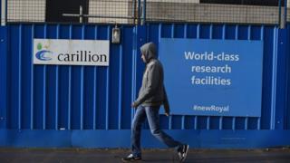 Man walks past Carillion building site