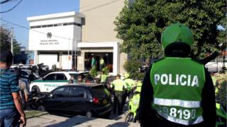 A helmeted policeman in his bright green uniform looks at the police station as medical staff and other officers congregate in front of the station