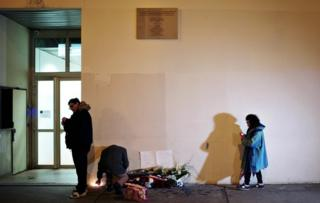 People light candles outside satirical newspaper Charlie Hebdo former office, in Paris, Wednesday, Jan. 6, 2016.