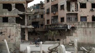 Suriyeli bir çocuk Duma'da yıkıntılar arasında bisiklet sürüyor