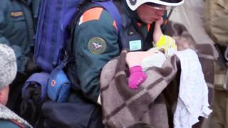 Rescuers pull an 11-month old baby girl from the rubble of an apartment block explosion in Magnitogorsk