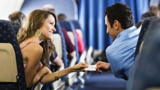 Mulher e homem a bordo de avião, trocando telefones